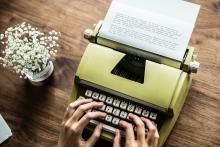 two hands typing on a bright green typewriter