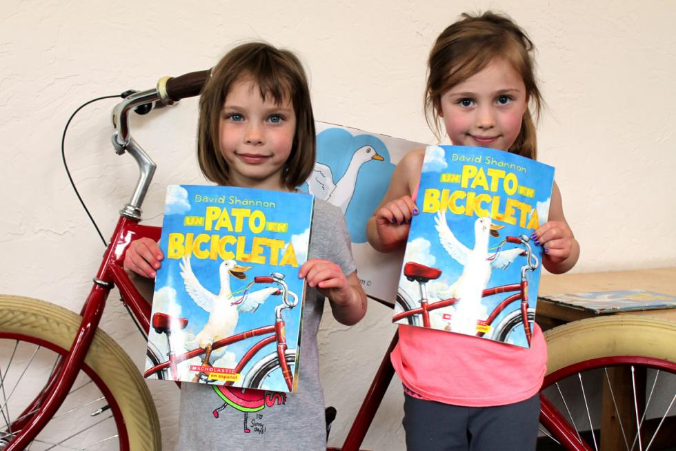 Two girls holding up children's book
